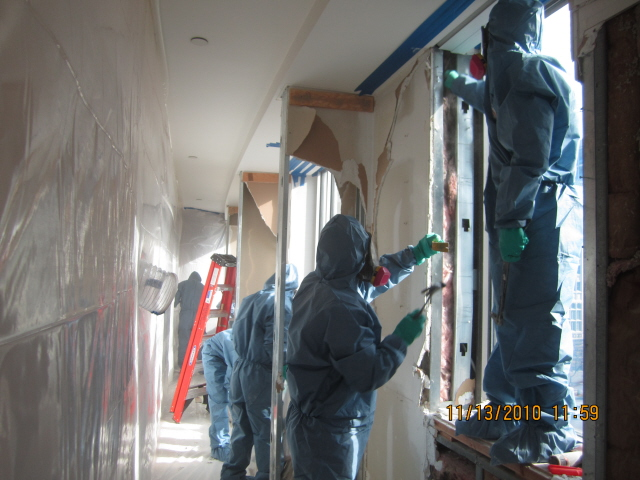 Workers in protective clothes and masks restoring drywall   Amerestore